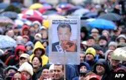 """Zaposleni u mađarskoj radio stanici Klubradio i njihove pristalice s plakatom s fotografijom mađarskog premijera Viktora Orbana na kome piše: """"Zar ne vidiš da je previše?"""" na protestu za slobodu govora u Budimpešti 24. februara 2013."""