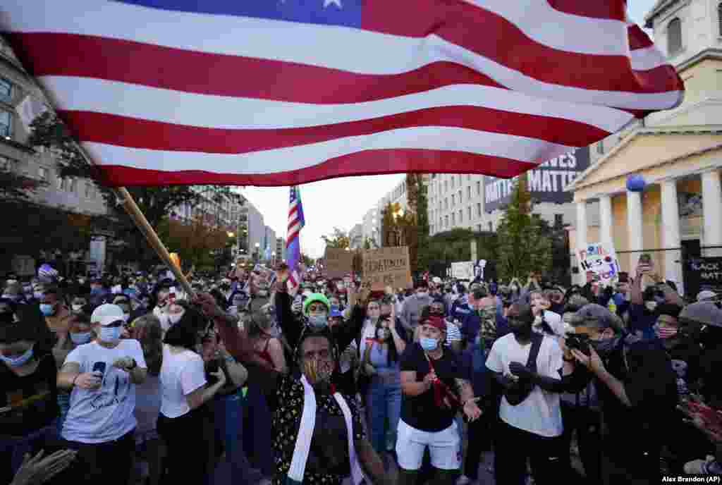 People gather in Black Lives Matter Plaza to celebrate president-elect Joe Biden's win over Pres. Donald Trump to become the 46th president of the United States, Saturday, Nov. 7, 2020, in Washington. His victory came after more than three days of uncertainty as election officials sorted through a surge of mail-in votes that delayed the processing of some ballots.