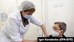 Женщина получает вакцину против коронавируса в одном из ЦСМ Бишкека.