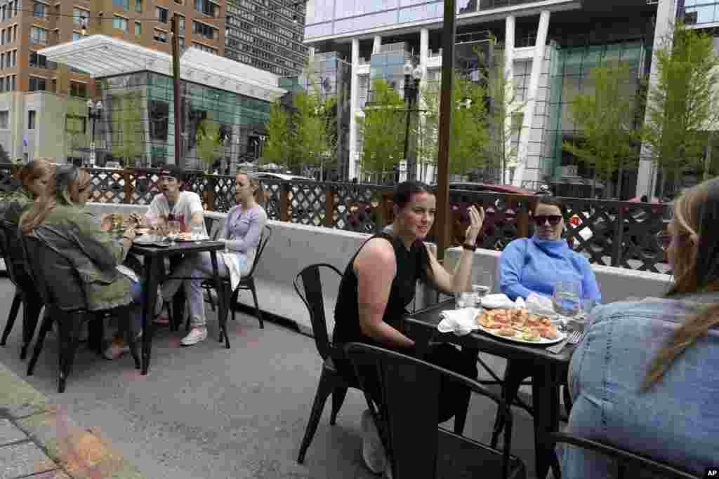 Clienții unui restaurant conversează și iau masa fără măști, duminică, 2 mai 2021, în Boston. În Massachusetts începând de vineri, 30 aprilie 2021, măștile sunt necesare în aer liber numai atunci când nu este posibil să se mențină o distanță de aproximativ 1,5 metri între persoane (Foto AP / Steven Senne)