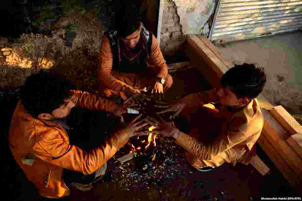 Afghan people gather around a fire to beat the cold in Jalalabad. (epa-EFE/Ghulamullah Habibi)