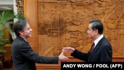 АҚШ мемлекеттік хатшысының орынбасары болып тұрған кездегі Энтони Блинкен Қытай сыртқы істер министрі Ван Имен қол алысып тұр. Пекин, 2015 жыл.