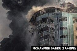 Füst száll fel 2021. május 15-én, amikor egy izraeli légicsapás nyomán összeomlik az Al-Dzsalaa toronyház, amely lakásoknak és több médiaszervezetnek, köztük az Associated Pressnek és az Al Jazeerának adott otthont Gáza városában.