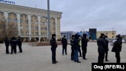 Пикет өткізуші әйелді жан-жақтан қоршап тұрған полиция қызметкерлері. Қызылорда, 12 қаңтар 2021 жыл.