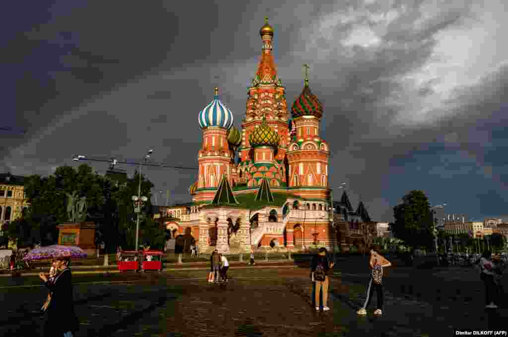 People walk in front of St. Basil's Cathedral lit by the sun with a rainbow in the background on Red Square in Moscow. (AFP/Dimitar Dilkoff)
