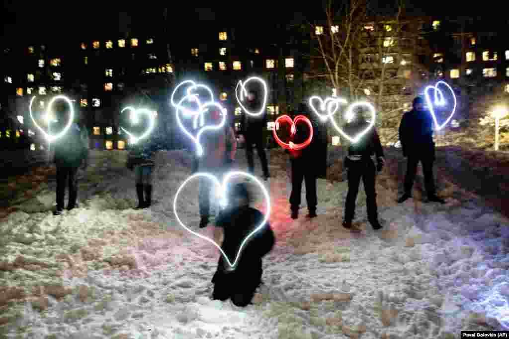 """Oamenii """"desenează"""" inimi cu lanternele de la telefonul mobil în sprijinul liderului opoziției, condamnat la închisoare, Alexei Navalnîi, și aj soției sale, Iulia Navalnîia, la Moscova în noaptea de 14 februarie, sub sloganul: """"Iubirea este mai puternică decât frica""""."""