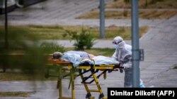 РУСИЈА - Медицинско лице придружува жена во болница каде се лекуваат пациенти од КОвид-19. 30 јуни 2021 година.