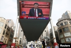 A giant screen shows Chinese President Xi Jinping attending the closing session of the National People's Congress at the Great Hall of the People in Beijing on March 11.