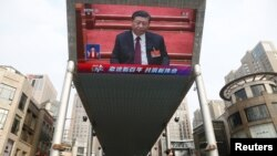 A giant outdoor screen shows Chinese President Xi Jinping attending the closing session of the National People's Congress in Beijing on March 11.