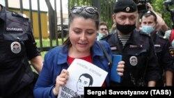 Un poliștist o reține pe o participantă la o acțiune de pichetare pentru susținerea lui Ivan Safronov, un fost jurnalist și adjunct al șefului agenției spațiale Roscosmos, care rămâne în arest fiind acuzat de trădare, Moscova, 13 iulie 2020.