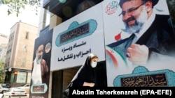 Жена поминува покрај огромен постер на кој е претставен иранскиот претседателски конзервативен кандидат Ебрахим Раиси, Техеран, на 31 мај 2021 година