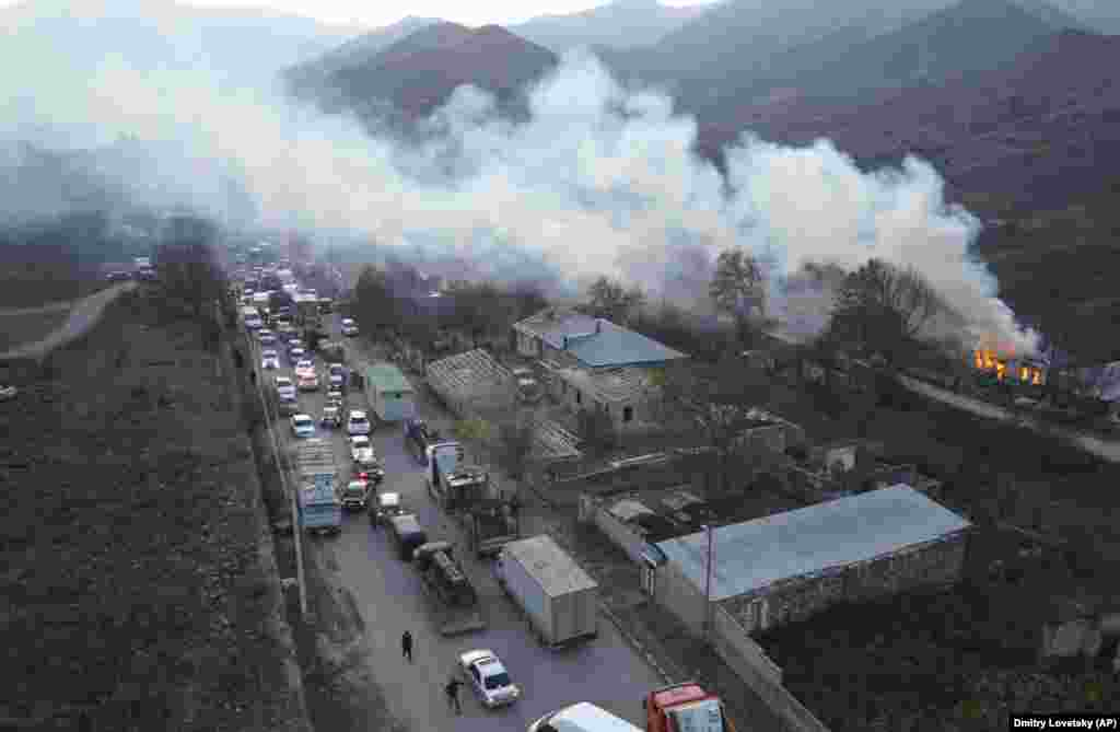 Smoke from a burning house drifts over a traffic jam as ethnic Armenians flee Karvachar/Kalbacar – which is internationally recognized as part of Azerbaijan. Ethnic Armenians point to ancient Christian monuments in the area that mark their historic ties to the land.