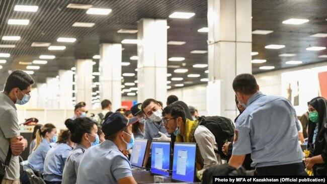 Пассажиры спецборта из Кабула и сотрудники Погранслужбы в аэропорту Алматы