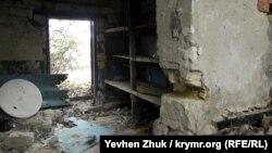 Развалины печки в углу, старые стеллажи и мусор