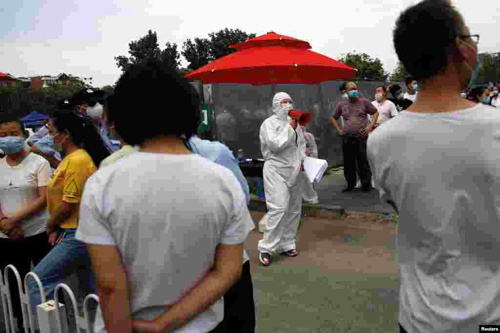 A medical worker in a protective suit holds a loudspeaker as people line up outside a site for nucleic acid tests, following new cases of coronavirus disease (COVID-19) infections in Beijing, China June 17, 2020. ​China reported several dozen more coronavirus infections Tuesday as it increased testing and lockdown measures in parts of the capital to control what appeared to be its largest outbreak in more than two months.