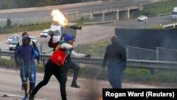 Сторонники бывшего президента ЮАР Джейкоба Зумы перекрыли автостраду горящими шинами во время акции протеста, ЮАР, 9 июля 2021 года