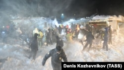 Video released by Russia's Emergency Situations Ministry showed rescuers working during the night to shovel snow off a building that had been buried.