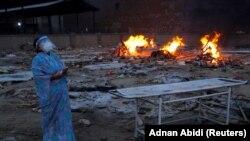 Женщина оплакивает своего мужа, умершего от COVID-19, в крематории в Нью-Дели, Индия. 5 мая 2021 года.