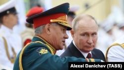 Президент Росії Володимир Путін (праворуч) і міністр оборони Сергій Шойгу на глядацьких трибунах під час Головного військово-морського параду на честь Дня Військово-морського флоту Росії. 25 липня 2021 року