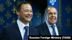 All smiles, for now: Russian Foreign Minister Sergei Lavrov (right) welcomes his Kyrgyz counterpart, Ruslan Kazakbaev, to Moscow on October 23.