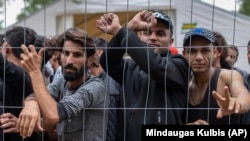 Migrants stand behind a fence inside a newly built refugee camp in Lithuania on August 4.