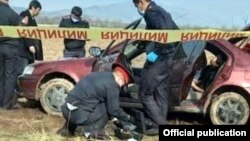 Police carry out investigations on the car in which the bodies were found.