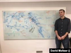 """Evolutionary biologist Greger Larson flanks a whiteboard in his office at Oxford as he and his co-authors """"turn it into a palimpsest"""" in November 2018 for their PNAS study. Human events are marked in blue and dog events in orange, with northeast Asia on the left and North America on the right. Co-author David Meltzer says it's """"what scientific convergence sometimes looks like."""""""