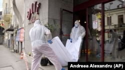 Forensic workers carry the body of Gholamreza Mansuri from a hotel downtown Bucharest, June 19, 2020