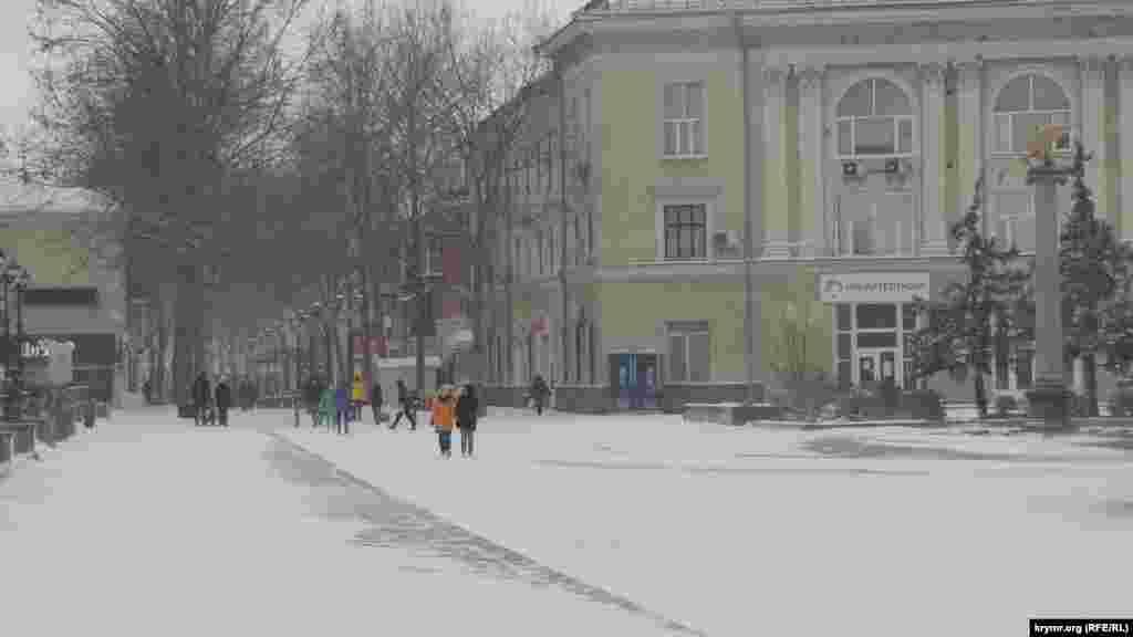 Улица Ленина запоминается многим туристам как одна из самых тенистых в центре Керчи: летом здесь приятно гулять под сенью платанов. Сейчас силуэты деревьев и ряды фонарей смотрятся непривычно на фоне белого снега