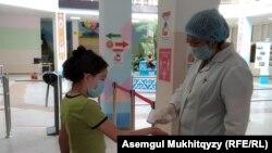 Медсестра, измеряющая температуру школьника у входа в гимназию № 67. Нур-Султан, 27 августа 2020 года.