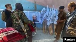 Militantët talibanë shikojnë një poster me portretin e liderit të tyre Mullah Haibatullah Akhundzada. Kabul, 25 gusht 2021.