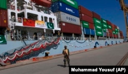 A security guard stands outside a ship at the port of Gwadar, which has been leased to a Chinese corporation by the Pakistani government.