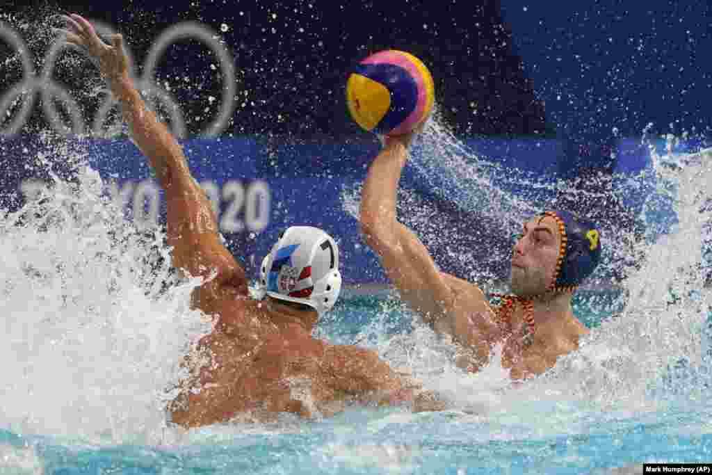 Страхиня Расович из Сербии (слева) блокирует удар испанца Берната Санахуджи (справа) во время матча предварительного раунда по водному поло среди мужчин на летних Олимпийских играх 2020 года, воскресенье, 25 июля 2021 года, в Токио, Япония