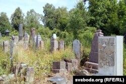 Другі абэліск з аскепкаў на фоне надмагільных помнікаў, якія чакаюць рамонту