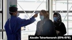 Тегеран аэропортунда жүргүнчүлөрдү учакка салардан мурунку текшерүү. Август, 2020-жыл.