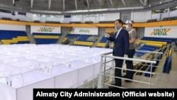 Almaty Mayor Bakytzhan Sagintayev (left) inspects the construction of a temporary COVID-19 hospital in the Halyq Arena in Almaty. (file photo)