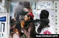 Боец «Талибана» проходит мимо салона красоты, с закрашенными женскими лицами. Кабул, Афганистан