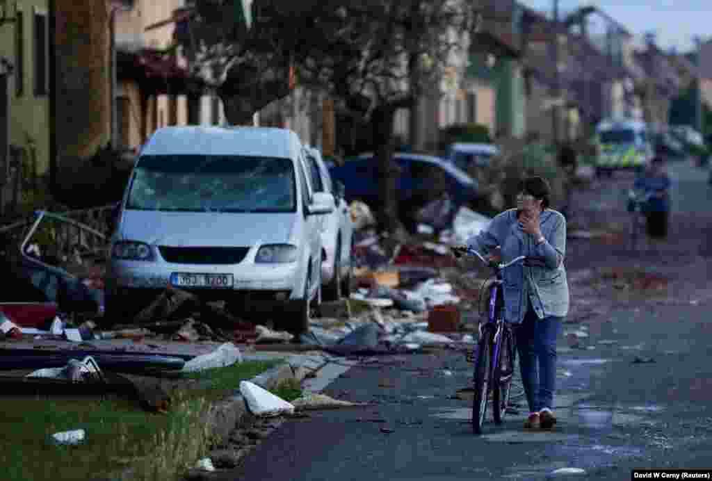 Люди проходять повз сміття на вулиці після торнадо, село Моравська Нова Вес, 25 червня 2021 року