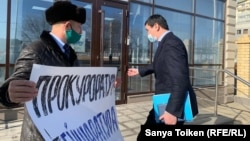 Адвокат Айбар Косымбаев перед зданием областной прокуратуры с плакатом: «Прокуратура. Бейшаратура». Атырау, 5 февраля 2021 года.