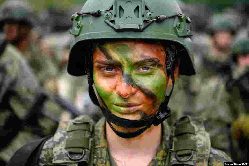 Косовская солдат позирует фотографу после участия в многонациональных учениях под руководством США в деревне Дева, Косово, 28 мая