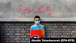 """Băiat iranian cu o caricatură a lui Emmanuel Macron, sub o inscripție """"Slavă profetului Mahomed' în timpul unei manifestații antifranceze în fața ambasadei Franței din Teheran, octombrie 2020"""