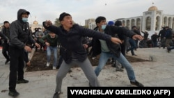 Supporters of Sadyr Japarov throw clumps of dirt toward supporters of former Kyrgyz President Almazbek Atambayev as they attend a rally in Bishkek on October 9.