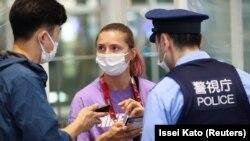 Белорусская спортсменка Кристина Тимановская беседует с полицейским в международном аэропорту Ханеда в Токио, 1 августа 2021 года