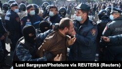 A man is taken away by law enforcement officers during an opposition rally to demand the resignation of Armenian Prime Minister Nikol Pashinian