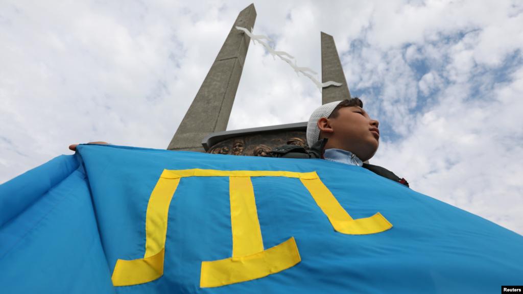 Мальчик держит флаг крымских татар на мероприятии, посвященному дню памяти жертв геноцида крымскотатарского народа, Евпатория