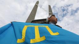 Кримські татари фотографуються з плакатами з нагадуванням про трагедію 1944 року та репресії