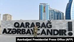 """Президент Илҳом Алиев """"Қорабоғ Озарбайжондир"""" деган тарғибот панноси олдида."""