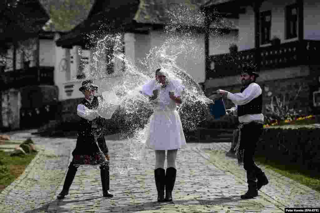 Dressed in folk costumes, young men pour water on a young woman in Holloko, a Hungarian mountain village that is on UNESCO's World Heritage list. Holloko is famous for its traditional Easter celebrations, but this year all the events have been canceled due to the coronavirus. (epa-EFE/Peter Komka)