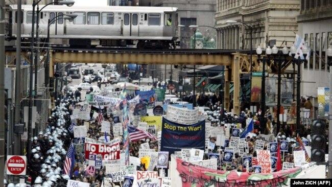 Сотни чикагских полицейских в спецодежде окружают группу из нескольких тысяч протестующих, идущих по Мичиган-авеню, под рельсами «EL», 5 апреля 2003 года в Чикаго, штат Иллинойс.