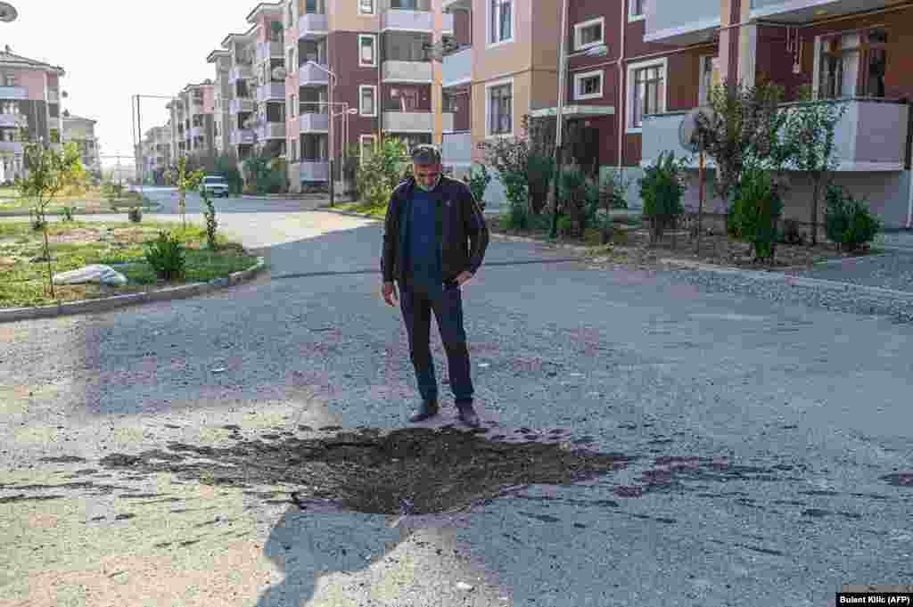 Мужчина смотрит на воронку, образовавшуюся после попадания снаряда на дороге в Тартаре, недалеко от передовой продолжающегося конфликта. 18 октября 2020 года.
